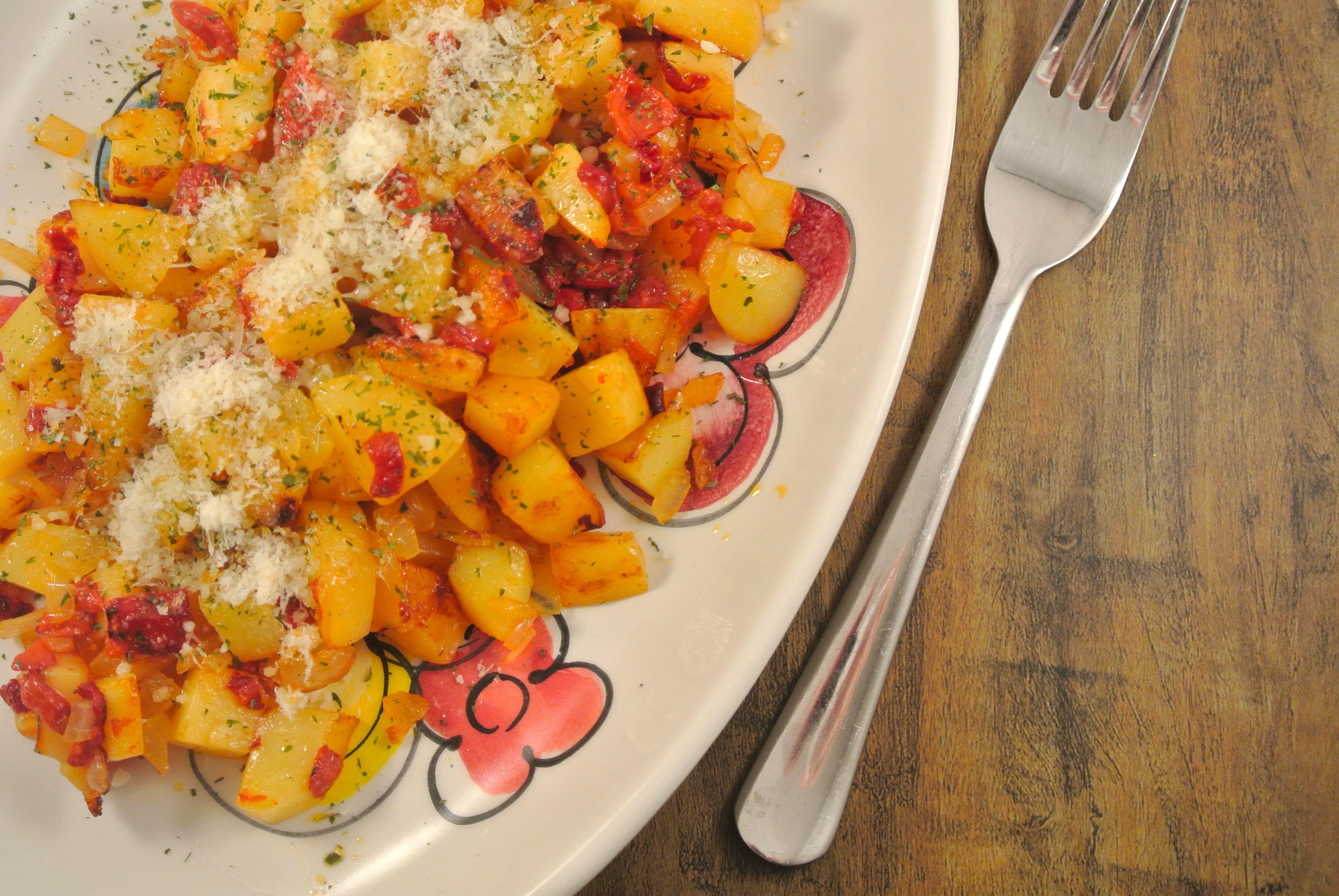 Gebakken aardappeltjes met geroosterde paprika en ui